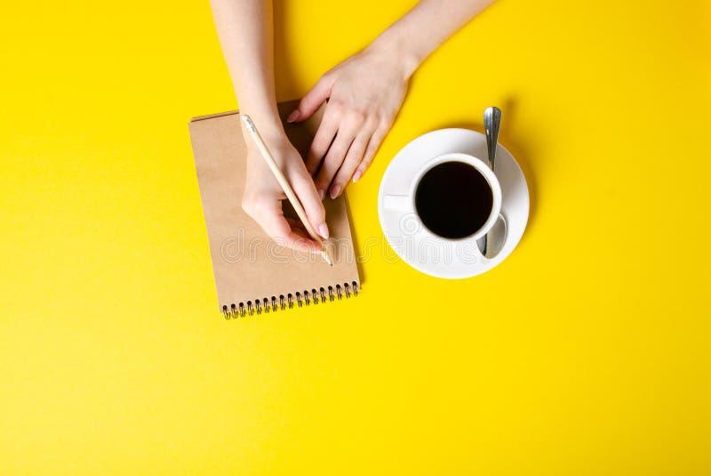 Xícara de café, bloco de notas, lápis, mãos fêmeas foto de stock