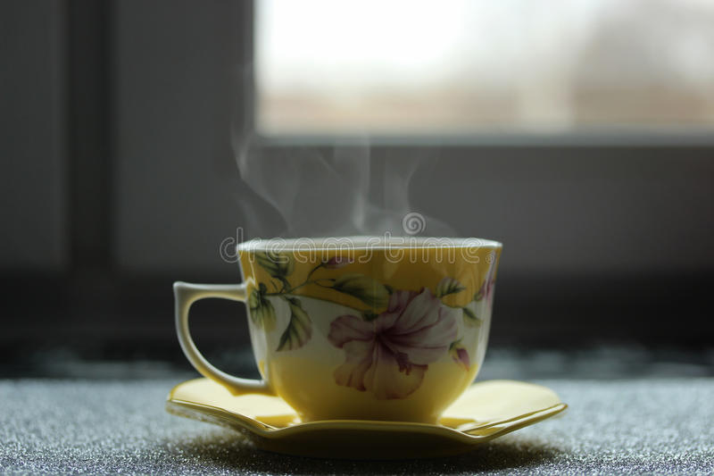Xícara de café bonita e quente com os pires perto da janela cedo na manhã fotos de stock royalty free