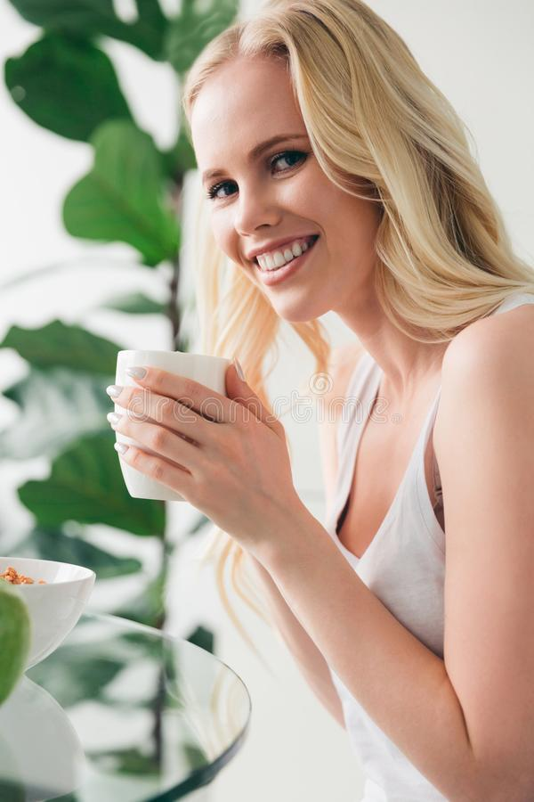 xícara de café bonita e sorriso da terra arrendada da jovem mulher foto de stock royalty free
