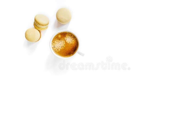 Xícara de café branca com macarons amarelos imagem de stock