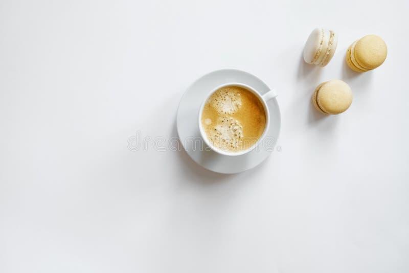 Xícara de café branca com macarons amarelos fotografia de stock