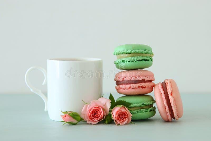 Xícara de café branca do vintage e macaron ou bolinho de amêndoa colorido sobre a tabela de madeira pastel imagens de stock royalty free