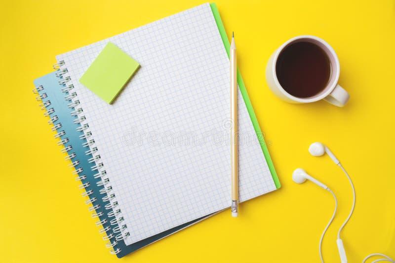 Xícara de café branca limpa do caderno e do lápis com espaço da cópia no fundo amarelo da tabela para a apresentação, o escritor  foto de stock