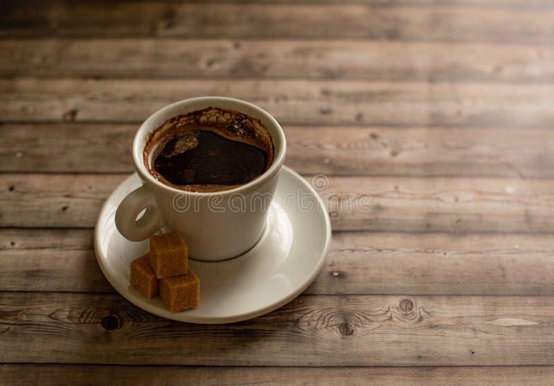 A xícara de café branca nas partes de madeira do açúcar de bastão do fundo natural plat sobre foto de stock royalty free