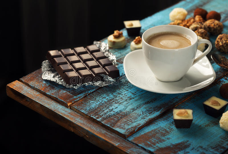 Xícara de café com barra de chocolate e variedade de doces foto de stock royalty free