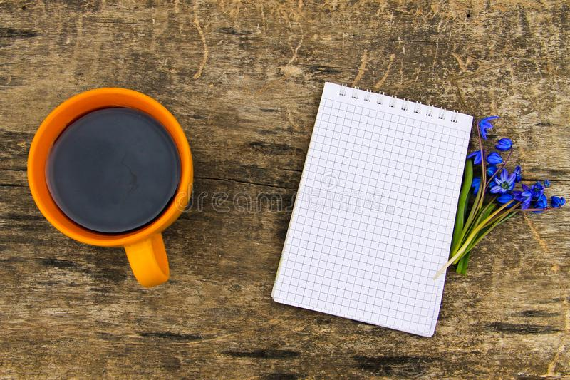 A xícara de café com bloco de notas e o scilla azul floresce na mesa de madeira fotos de stock