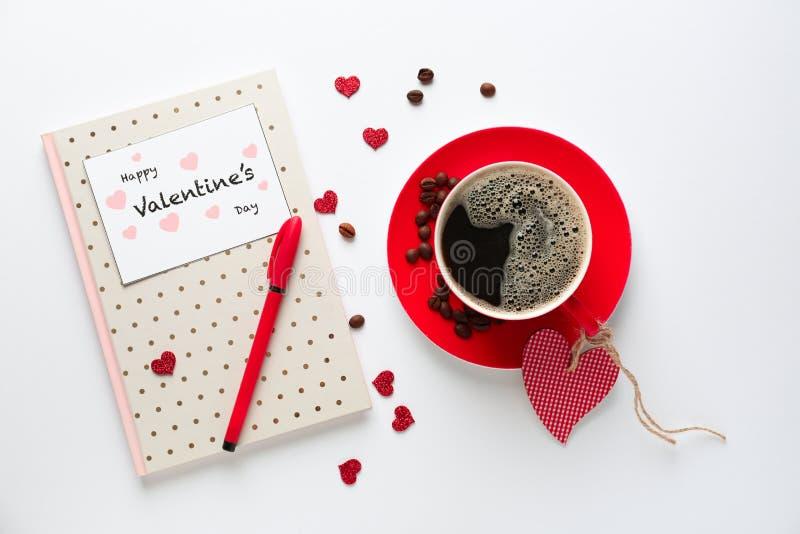 Xícara de café com caderno e Valentim \ 'cartão do dia de s no fundo branco fotos de stock