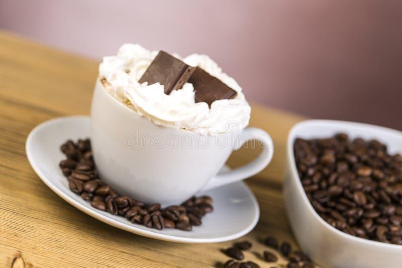 Xícara de café com chantiliy e chocolate imagens de stock royalty free
