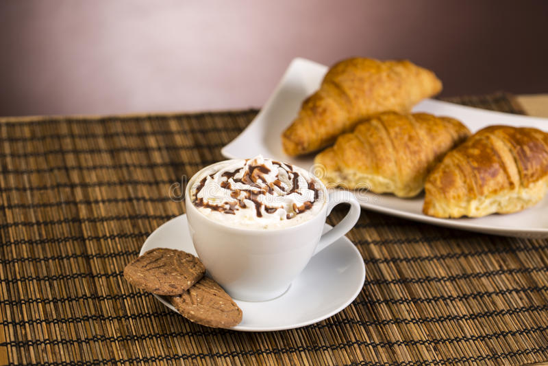 Xícara de café com chantiliy e croissant imagem de stock
