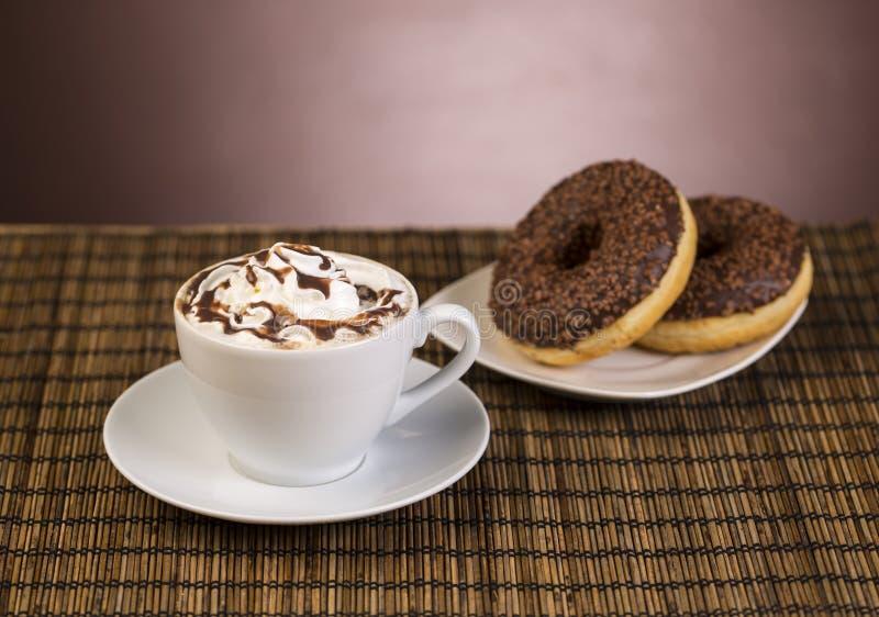 Xícara de café com chantiliy e filhós foto de stock