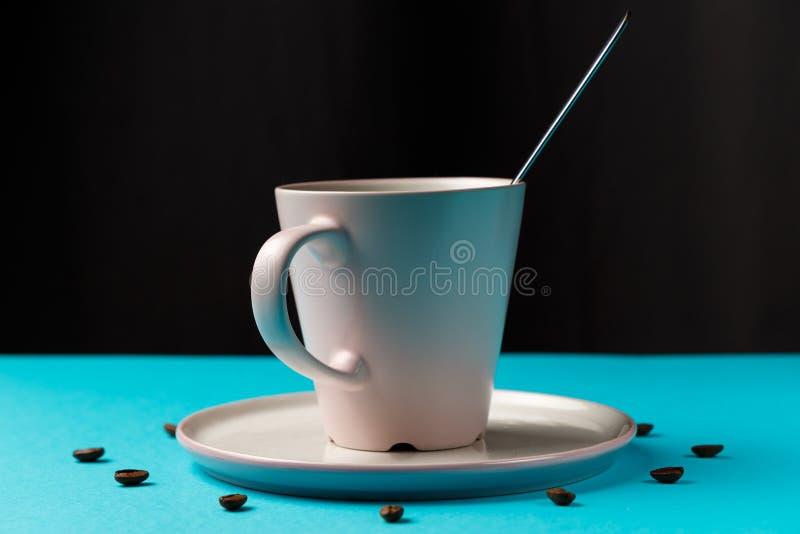 Xícara de café com colher em pau e feijão de café contra fundo azul formando discagem de relógio Café como símbolo da energia da  imagens de stock royalty free