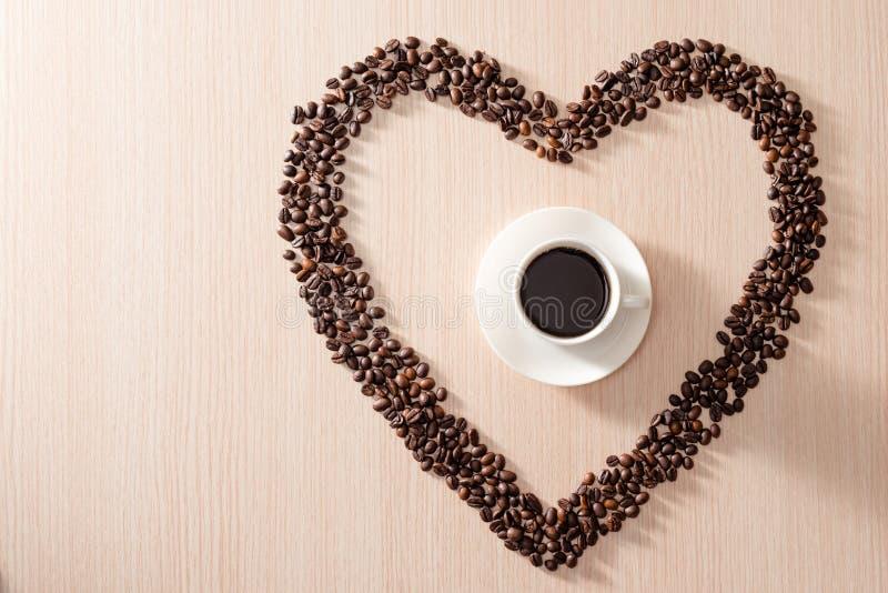 Xícara de café com feijão torrado amava sobre fundo de madeira foto de stock royalty free