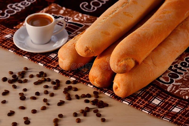 Xícara de café com feijões de café e baguette foto de stock