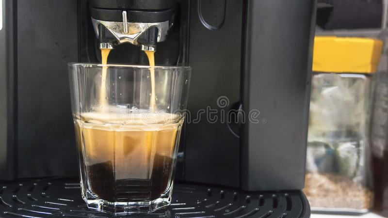 Xícara de café com gota da água do feijão à máquina do café dentro imagens de stock