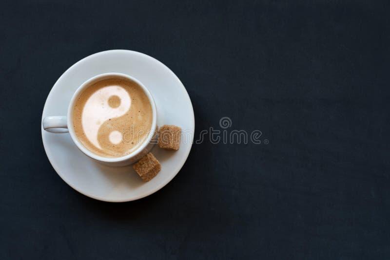 Xícara de café com leite, açúcar de bastão e sinal de yin-Yang no fundo escuro Vista superior Copie o espaço imagens de stock royalty free