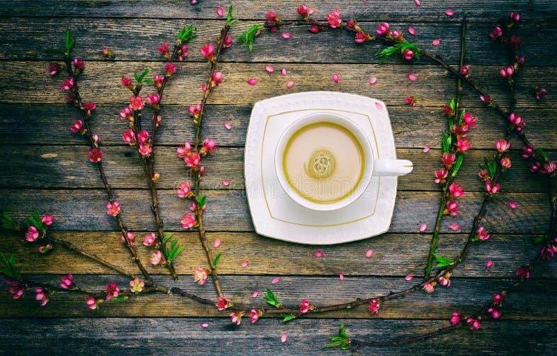 A xícara de café com leite e um quadro do pêssego ramifica com as flores cor-de-rosa no fundo de madeira das placas do celeiro fotos de stock royalty free