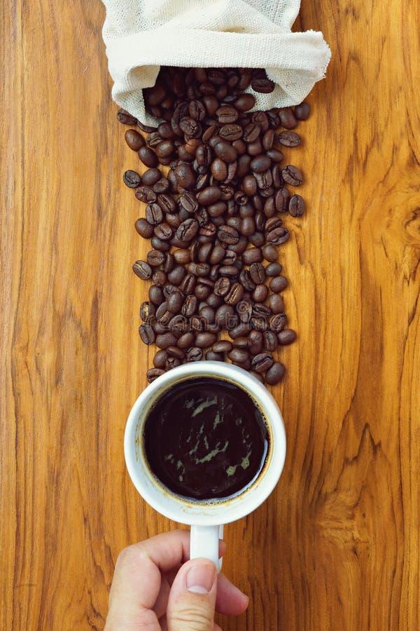 Xícara de café com o saco do feijão de café no fundo de madeira da textura imagens de stock