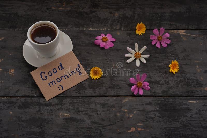 Xícara de café com sinal do bom dia e flores na tabela imagens de stock royalty free