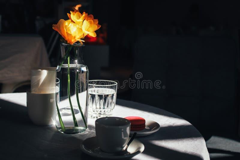 Xícara de café com um ramalhete do narciso amarelo fotografia de stock royalty free