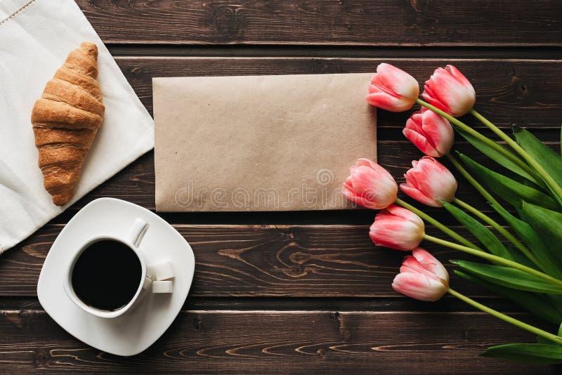 Xícara de café com um ramalhete de flores cor-de-rosa da tulipa e de um croissant para o café da manhã da manhã fotografia de stock