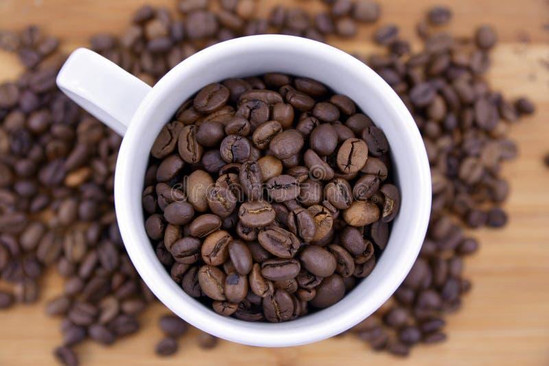 Xícara de café completamente de feijões de café fotos de stock