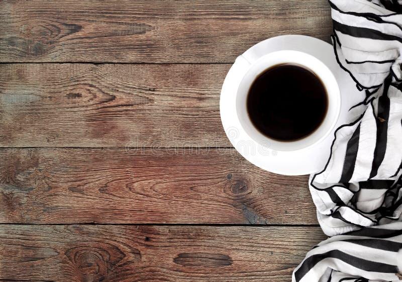 Xícara de café da manhã com o lenço feminino na tabela de madeira fotografia de stock royalty free
