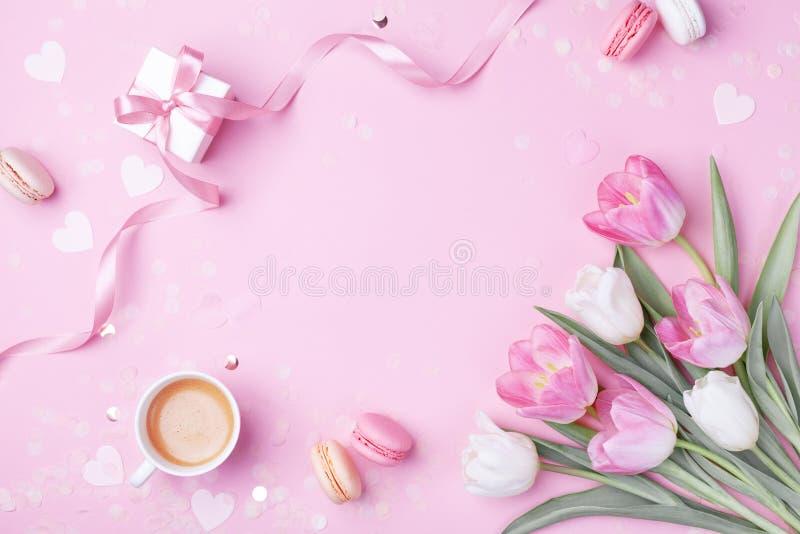 Xícara de café da manhã, macaron do bolo, presente ou caixa e flores atuais da tulipa da mola no rosa Café da manhã para mulheres fotografia de stock royalty free