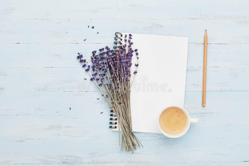 A xícara de café da manhã, o caderno limpo e a alfazema florescem na opinião superior do fundo azul Mesa de trabalho da mulher Co fotografia de stock royalty free