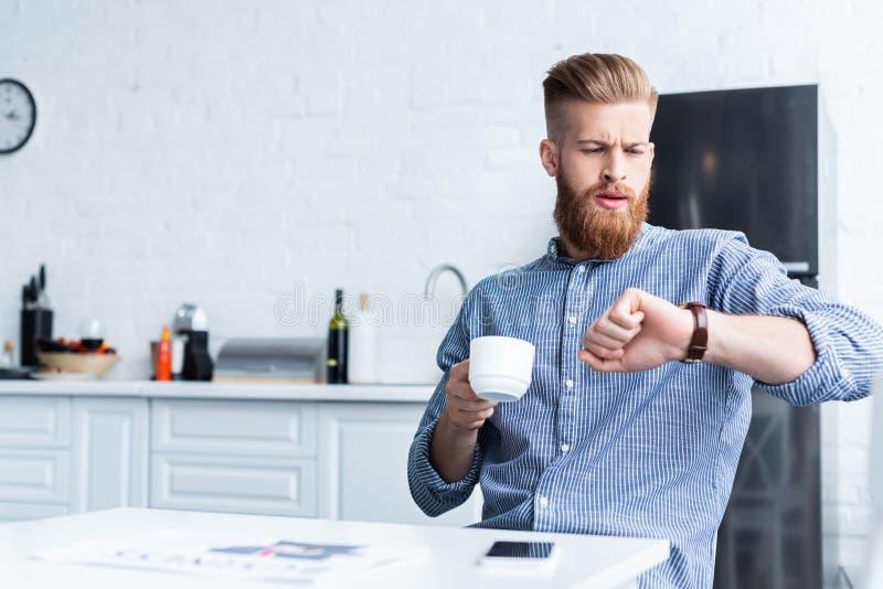xícara de café da terra arrendada do homem novo e relógio de pulso farpados consideráveis da verificação ao sentar-se imagens de stock royalty free