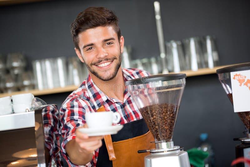 Xícara de café de oferecimento de sorriso do garçom fotografia de stock royalty free