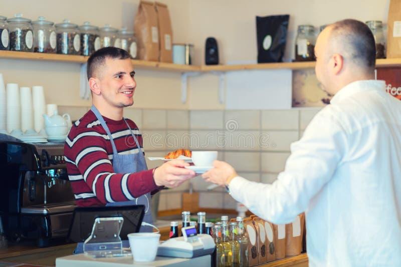 Xícara de café do serviço de Barista ao cliente no contador na cafetaria pequena imagens de stock