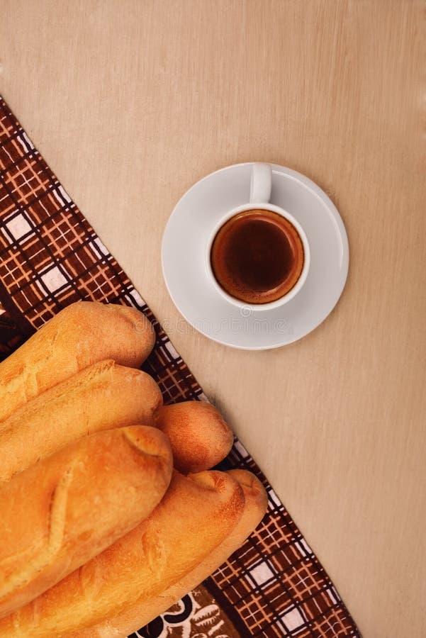 Xícara de café e baguette na tabela de madeira fotografia de stock royalty free