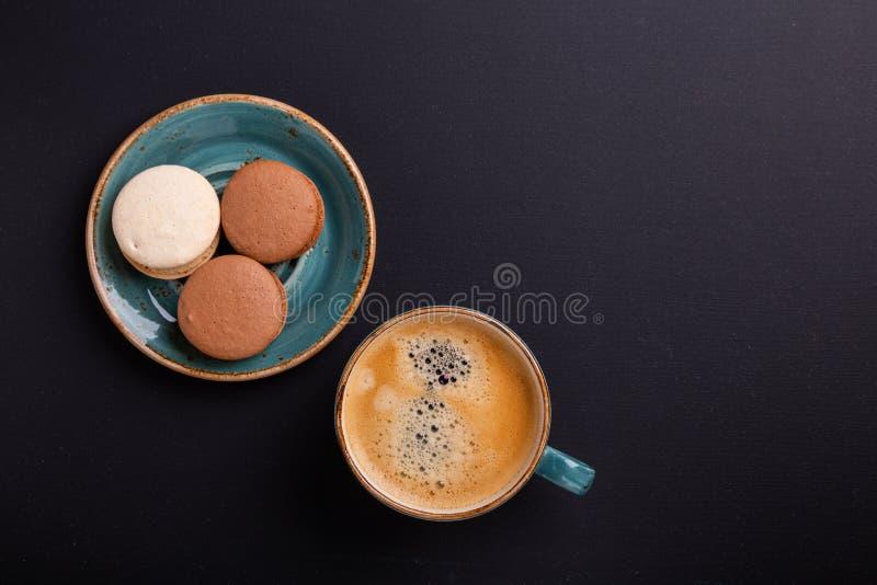 Xícara de café e bolinhos de amêndoa azuis na tabela de madeira escura Ruptura de Coffe Vista superior imagens de stock