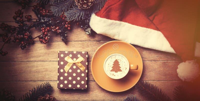 Xícara de café e caixa de presente com pinho e chapéu na tabela imagens de stock royalty free