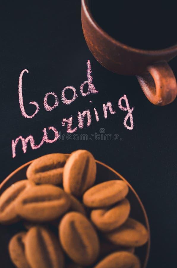 Xícara de café e cookie em um fundo escuro Bom dia da inscrição foto de stock