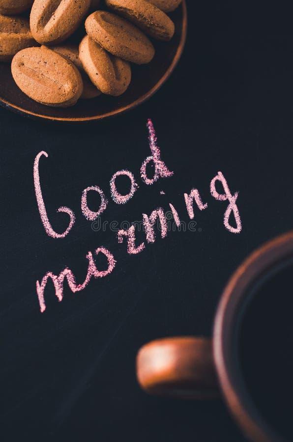 Xícara de café e cookie em um fundo escuro Bom dia da inscrição foto de stock royalty free