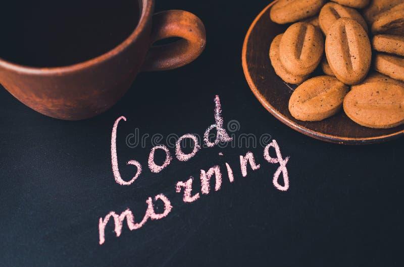 Xícara de café e cookie em um fundo escuro Bom dia da inscrição imagem de stock royalty free