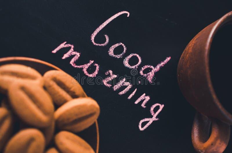 Xícara de café e cookie em um fundo escuro Bom dia da inscrição imagem de stock