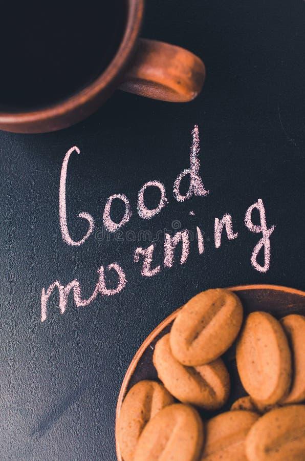 Xícara de café e cookie em um fundo escuro Bom dia da inscrição imagens de stock royalty free