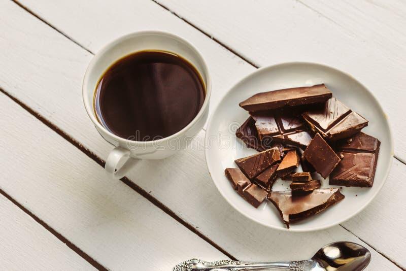Xícara de café e fatias de chocolate na placa fotografia de stock royalty free