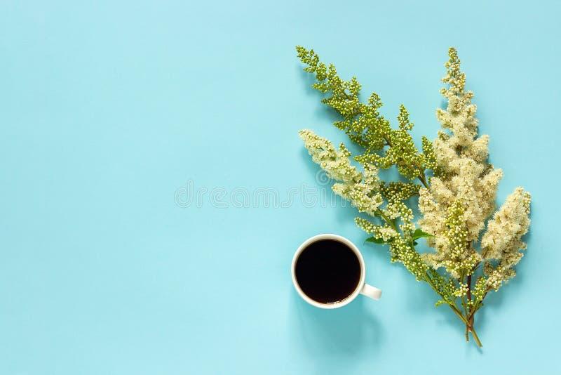 Xícara de café e flores brancas de florescência do galho no bom dia colocado plano de papel azul do conceito da opinião superior  fotos de stock royalty free