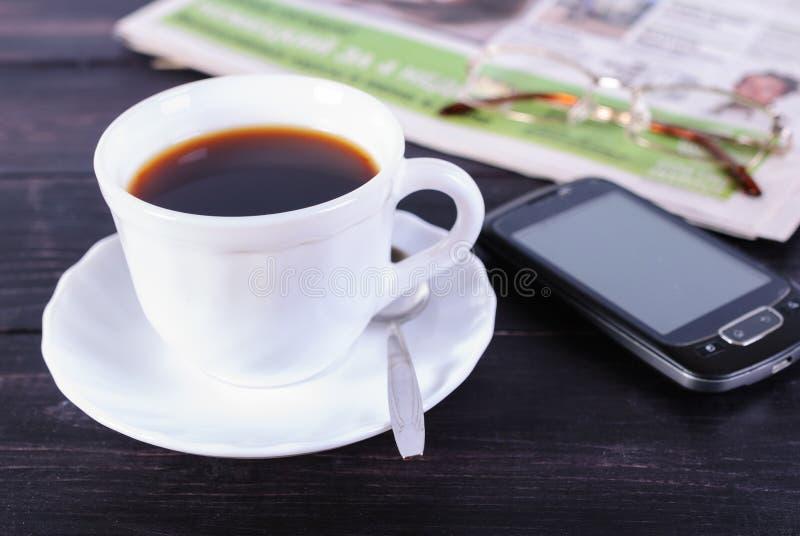 Xícara de café e jornal com vidros imagens de stock royalty free