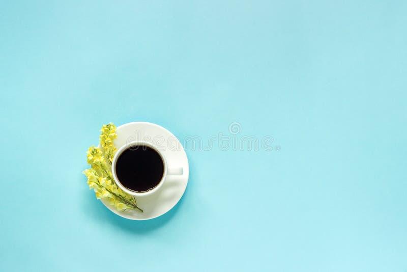 Xícara de café e Linaria amarelo das flores selvagens, bom dia colocado plano de papel azul do conceito da opinião superior do fu fotos de stock royalty free
