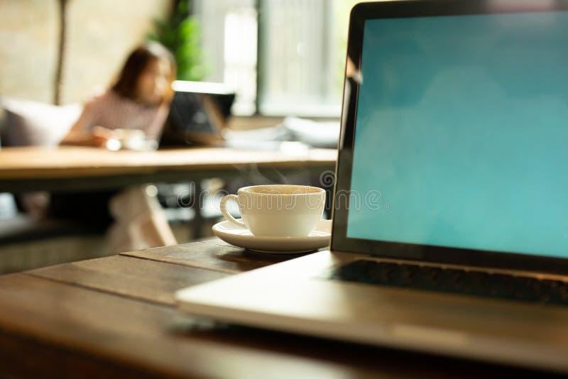 Xícara de café e portátil selecionados do foco na tabela com a mulher borrada que trabalha no fundo fotos de stock