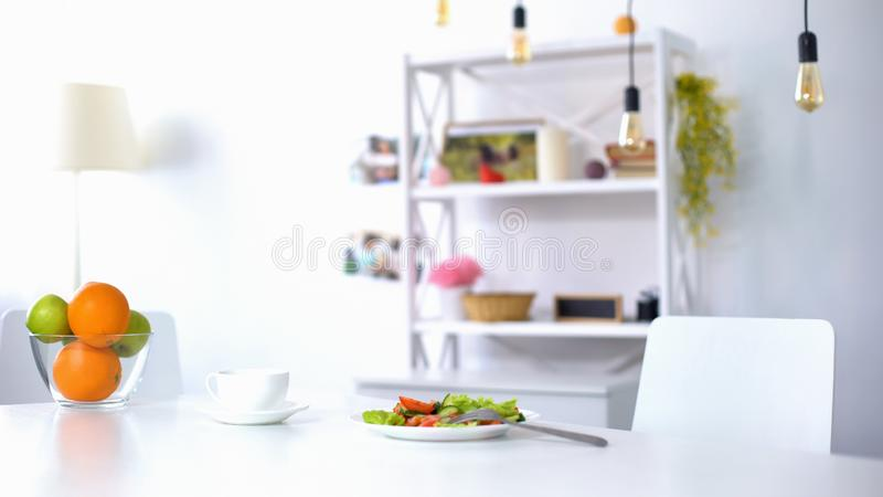 Xícara de café e salada fresca com vegetais e verdes na placa branca na tabela imagens de stock royalty free