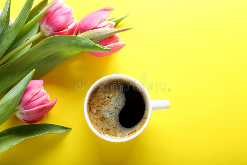 Xícara de café e tulipas cor-de-rosa no fundo amarelo, vista superior fotos de stock