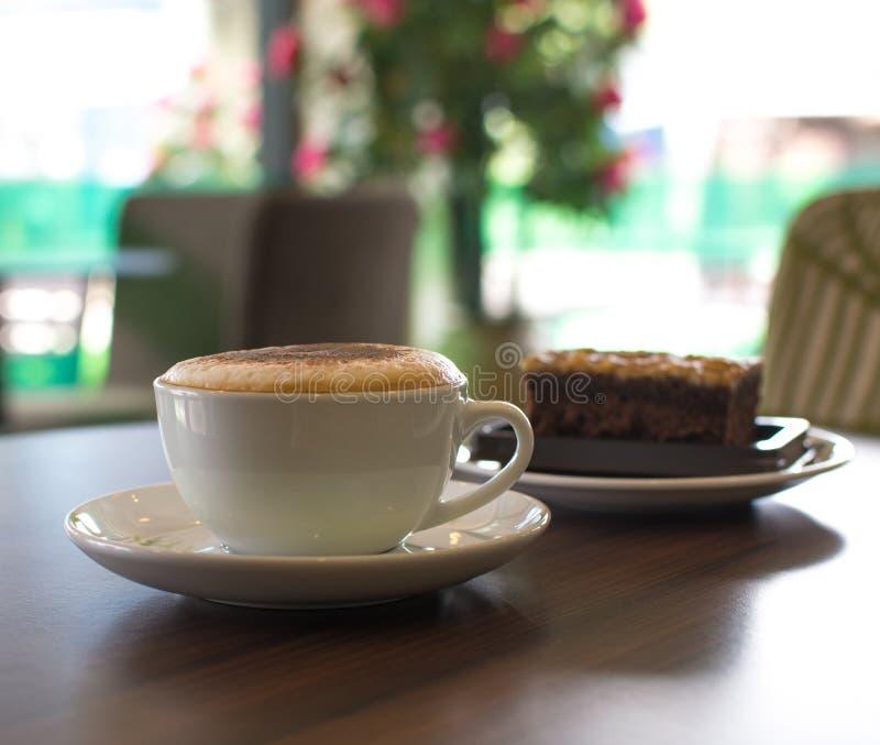 Xícara de café e um bolo na tabela no café imagens de stock