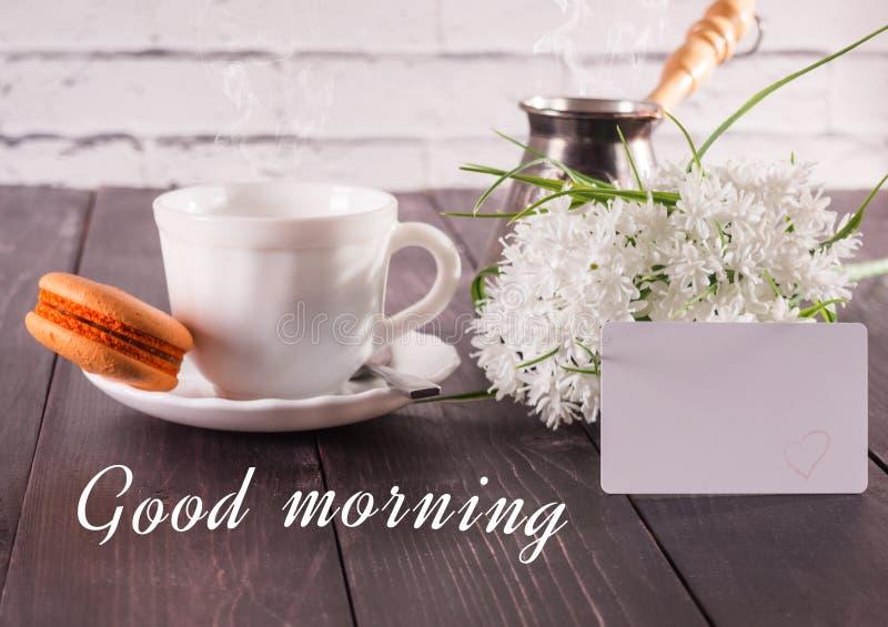 A xícara de café e um ramalhete das flores brancas em uma tabela e com um cartão a inscrição são um bom dia fotografia de stock