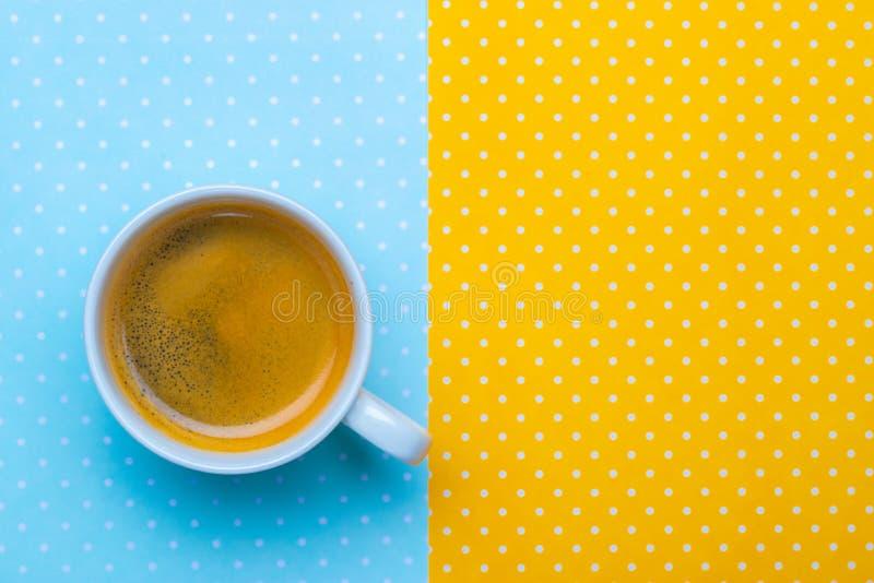 Xícara de café em um amarelo e em um fundo azul do às bolinhas imagem de stock