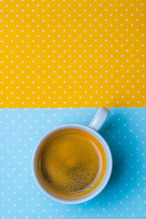 Xícara de café em um amarelo e em um fundo azul do às bolinhas foto de stock